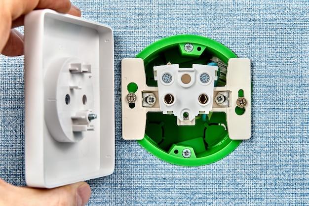 Der mechaniker repariert eine lose wandsteckdose oder eine steckdose des elektrischen heimsystems. Premium Fotos