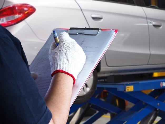 Der mechaniker überprüft das auto. Premium Fotos
