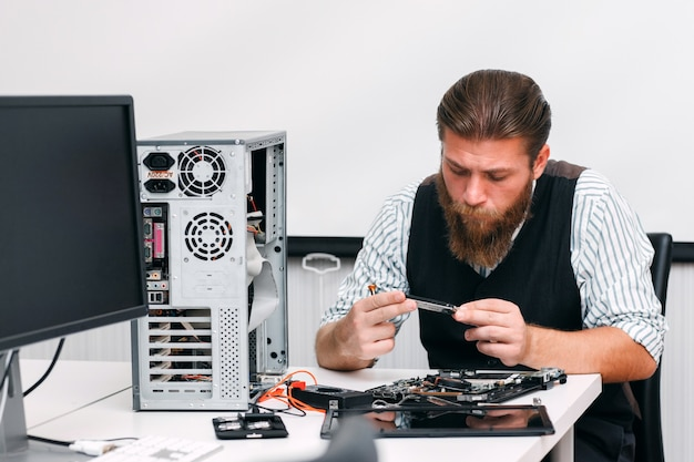 Der mechaniker untersucht den inneren teil des computers. ingenieur, der schaltung der zerlegten cpu in der reparaturwerkstatt betrachtet. elektronische renovierung, reparatur, entwicklungskonzept Premium Fotos