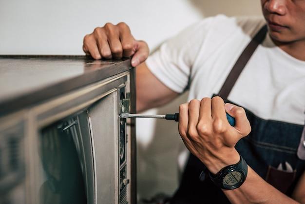 Der mechaniker zieht die schrauben am fernsehgerät mit einem schraubendreher fest. Kostenlose Fotos