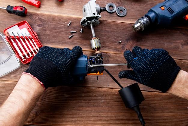 Der meister repariert ein defektes elektrisches gerät: bohrer, fräser auf einem holztisch. Premium Fotos