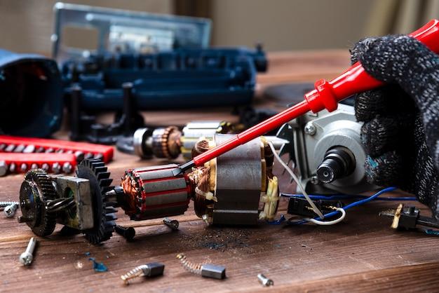Der meister repariert ein kaputtes elektrogerät: bohrmaschine, cutter auf einem holztisch. reparaturwerkstatt für elektrowerkzeuge Premium Fotos