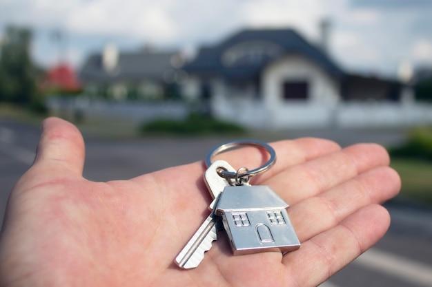 Der mensch hält die schlüssel zum haus in seinen händen Premium Fotos