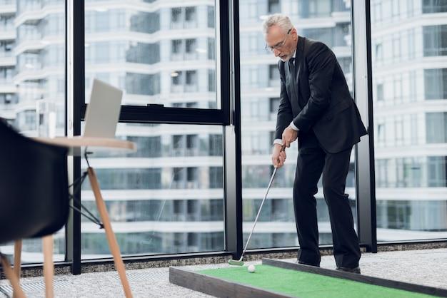 Der mensch steht im hintergrund des fensters und hält golfschläger Premium Fotos