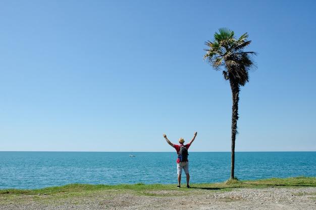 Der mensch steht mit den händen vor einer hohen palme mit meer und blauer himmel Premium Fotos