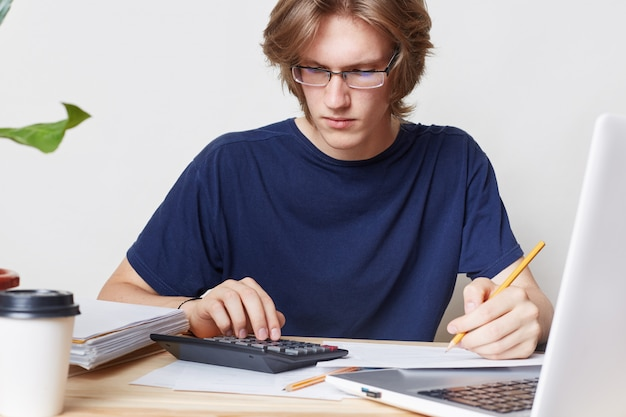 Der mensch steht vor einer finanzkrise, studiert die benachrichtigung der bank und berechnet die zahlen. männlicher student studiert mathematik, bereitet bericht vor Kostenlose Fotos