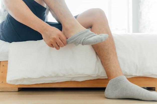 Der mensch trägt im schlafzimmer socken in die füße. konzept, fertig zu werden und sich zu verkleiden. Premium Fotos