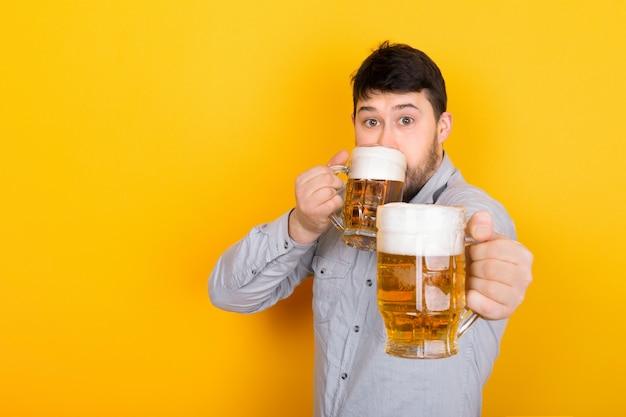Der mensch trinkt bier und bietet dem betrachter ein glas bier an Premium Fotos