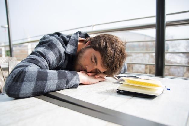 Der müde student, der mit seinem kopf schläft, ruhte auf tabelle aus Kostenlose Fotos