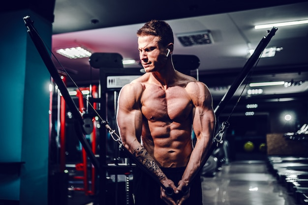 Der muskulöse bodybuilder, der an der turnhalle tut kastenfliege ausarbeitet, trainiert auf der drahtkabelmaschine Premium Fotos