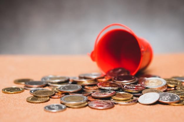 Der nahaufnahmestapel prägt vom roten eimer mit als geschäfts- und finanzkonzept verwirrend Premium Fotos