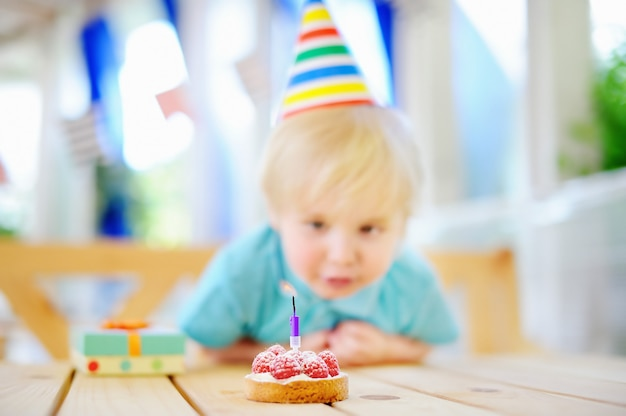 Der nette kleine junge, der spaß hat und feiern geburtstagsfeier mit bunter dekoration und kuchen Premium Fotos
