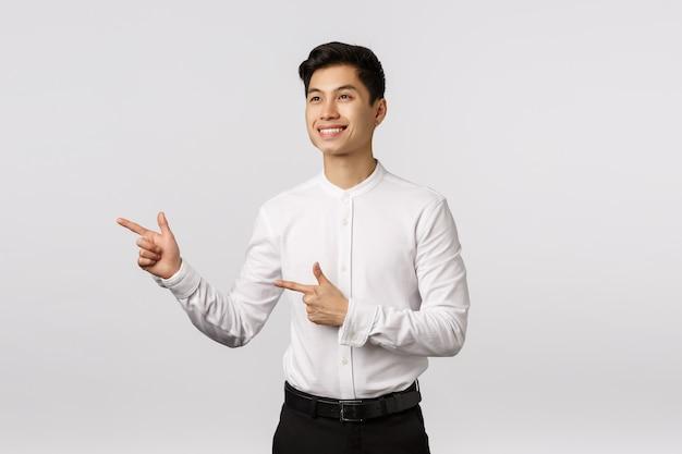 Der nette und entschlossene junge asiatische geschäftsmann bildete seinen verstand, treffen bereit entscheidung und zeigte das schauen nach links und das lächeln mit zustimmung, wie was er sieht und wählte großes produkt Premium Fotos