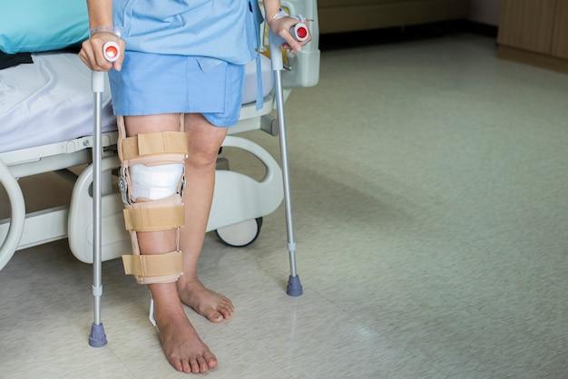 Der patient, der auf krücke in der krankenstation steht, ware knie-klammerunterstützung nach tun hintere kreuzbandoperation, verband auf knie von auf krücken. gesundheitswesen und medizinisches konzept. Premium Fotos