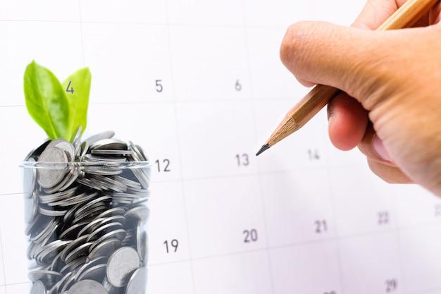 Der plan, in glas geld für ihre zukünftige investition zu sparen, ähnelt dem wachsen von grünen blättern Premium Fotos
