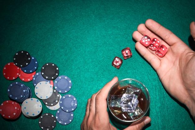 Der pokerspieler, der rot zeigt, würfelt mit glas whisky auf pokertisch Kostenlose Fotos