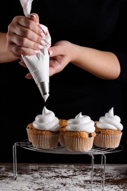 Der prozess der herstellung von cupcakes, beschichtung einer creme aus einem spritzbeutel in den händen eines konditor. Premium Fotos