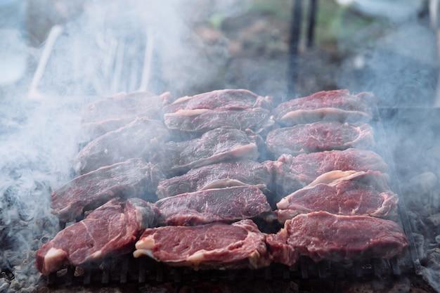 Der prozess des kochens von steakstücken auf dem grill. stücke gegrilltes und rohes fleisch. Premium Fotos