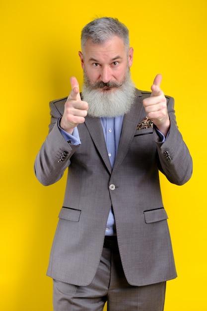 Der reife geschäftsmann des studio-porträts, gekleidet in den grauen anzug, zeigt auf kamera, ich wähle sie konzept, gelber hintergrund Premium Fotos