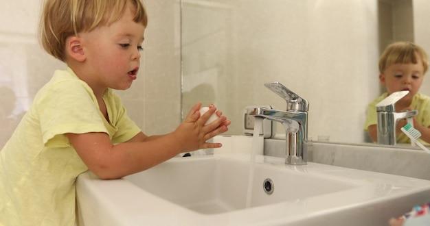 Der reizende kleine junge, der seife verwendet, um sich zu waschen, überreicht wanne nahe spiegel im stilvollen badezimmer Premium Fotos
