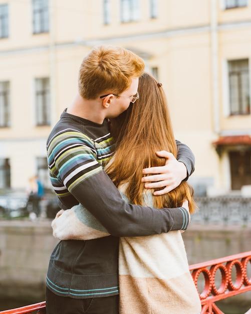Der rothaarige mann küsst eine frau auf den kopf, einen jungen in einem pullover Premium Fotos