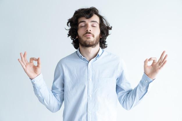 Der ruhige junge mann, der mit seinen augen meditiert, schloss Kostenlose Fotos