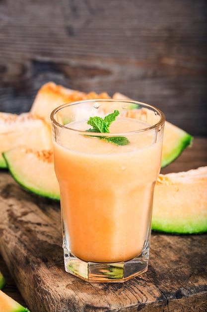 Der saft der melone mit minze in einem glasgefäß auf dem tisch. hamimelone Premium Fotos