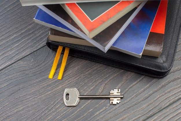 Der schlüssel liegt auf dem tisch vor dem hintergrund von büchern. metapher für die entdeckung von weisheit durch das studium der literatur Premium Fotos