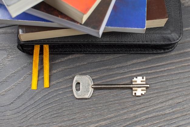 Der schlüssel liegt mit büchern auf dem tisch. metapher für die entdeckung von weisheit durch das studium der literatur Premium Fotos
