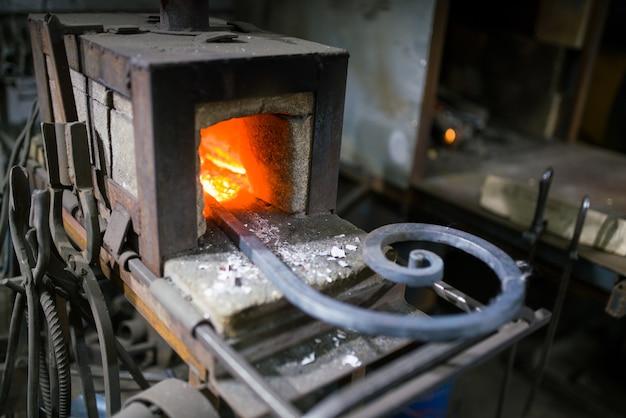 Der schmied schmiedet das leuchtende metall im ofen und wirft die funken aus Premium Fotos