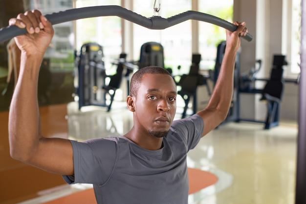 Der schwarze mann, der auf lat trainiert, ziehen maschine herunter Kostenlose Fotos