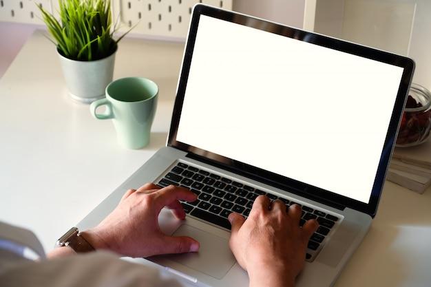 Der seitenansichtmann, der mit laptop arbeitet, ist auf der arbeitstabelle in einem conner-büro Premium Fotos