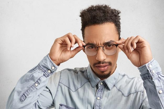 Der selbstbewusste männliche unternehmer gemischter rassen hält die brillenfassungen in den händen und sieht aufmerksam aus Kostenlose Fotos