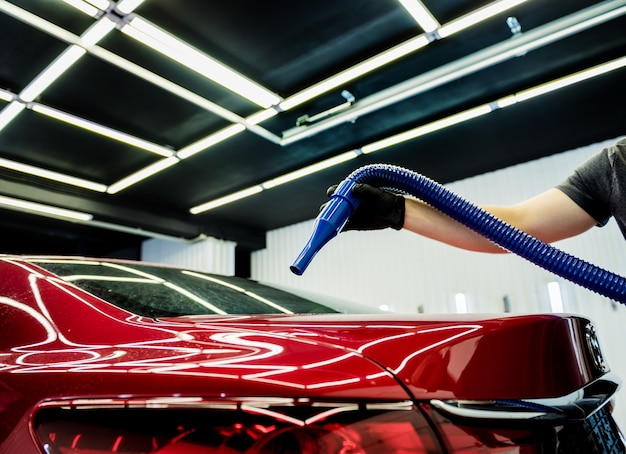 Der servicemitarbeiter trocknet das auto nach dem waschen automatisch. Premium Fotos