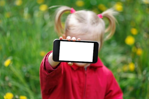 Der show smartphoneschirm des kleinen mädchens mit leerem weißem kopienraum. Premium Fotos