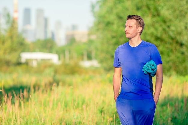 Der sportive junge mann, der sport tut, trainiert draußen im park Premium Fotos
