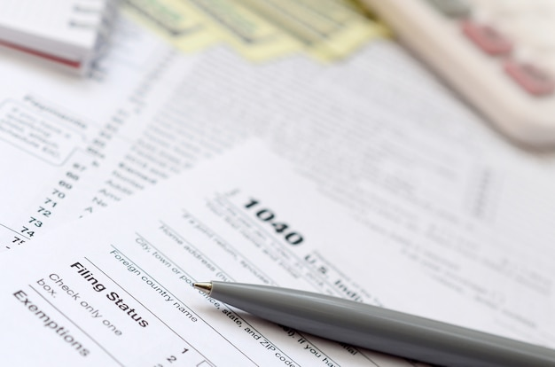 Der stift, das notizbuch, der taschenrechner und die dollarnoten liegen auf dem steuerformular 1040 us-einkommensteuererklärung. die zeit, um steuern zu zahlen Premium Fotos