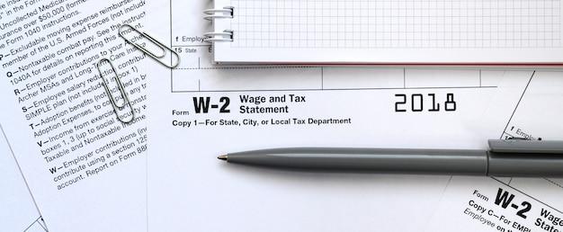 Der stift und das notizbuch auf dem steuerformular w-2 lohn- und steuererklärung. die zeit, um steuern zu zahlen Premium Fotos