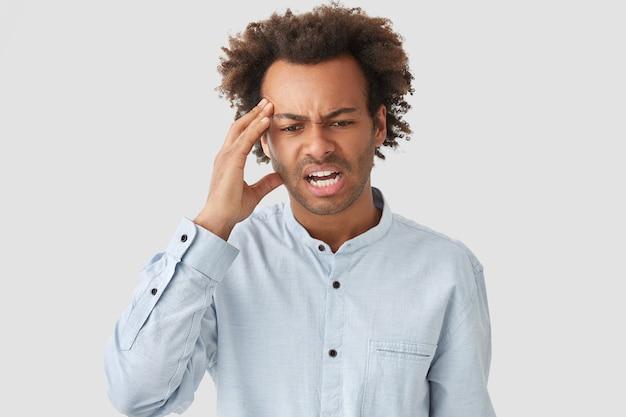 Der stressige junge afroamerikaner hält die hand an der schläfe, schaut verzweifelt nach unten, hat kopfschmerzen, lockiges haar, runzelt unzufrieden die stirn, trägt ein elegantes hemd und ist isoliert Kostenlose Fotos