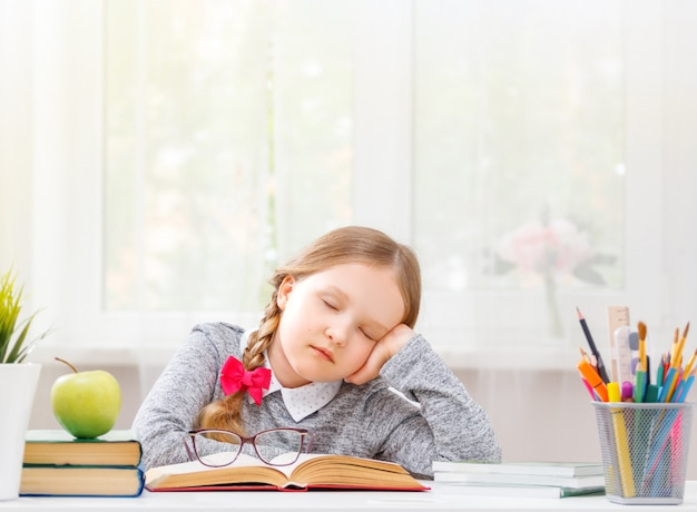 Der student, der am tisch saß, schlief bei dem buch ein. Premium Fotos