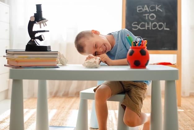 Der student sitzt am tisch und beschäftigt sich mit unterrichtsmaterial Premium Fotos