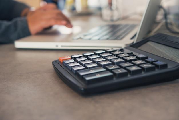 Der taschenrechner wird mit einem laptop auf einen bürotisch gestellt und das team arbeitet hinter den kulissen. Premium Fotos