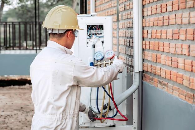 Der techniker der klimaanlage überprüft das luftkompressorsystem. Premium Fotos