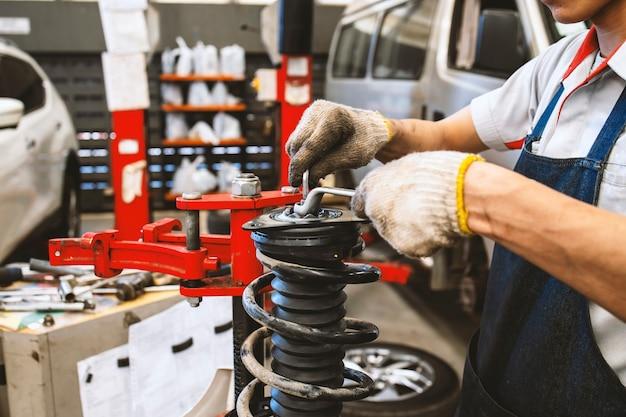 Der techniker repariert stoßdämpfer für kraftfahrzeuge mit weichzeichner und überlicht Premium Fotos