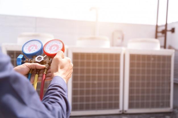 Der techniker überprüft die klimaanlage und die messgeräte zum befüllen der klimaanlagen. Premium Fotos