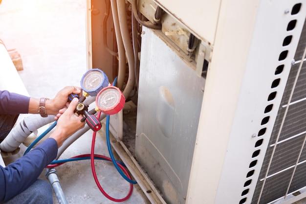 Der techniker überprüft die klimaanlage und misst die ausrüstung zum befüllen der klimaanlagen. Premium Fotos