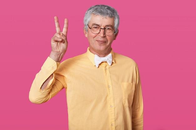Der temperierte alte senior zeigt mit zwei fingern nach oben Premium Fotos