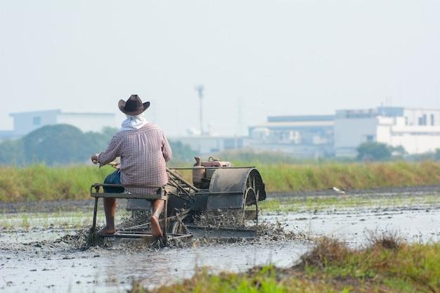 Der thailändische landwirt, der pinne traktor fährt, um reisfeld zu pflügen, bereiten neuen reis vor Premium Fotos