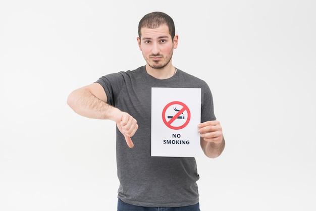Der traurige junge mann, der das nichtraucherzeichen hält, das daumen gestikulieren unten gegen weißen hintergrund Kostenlose Fotos