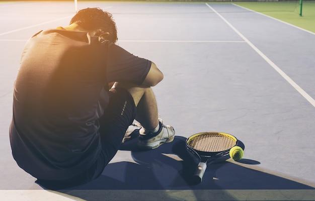 Der traurige tennisspieler, der im gericht nach sitzt, verlieren ein match Kostenlose Fotos